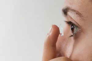 Woman with contact lens on finger ready to apply