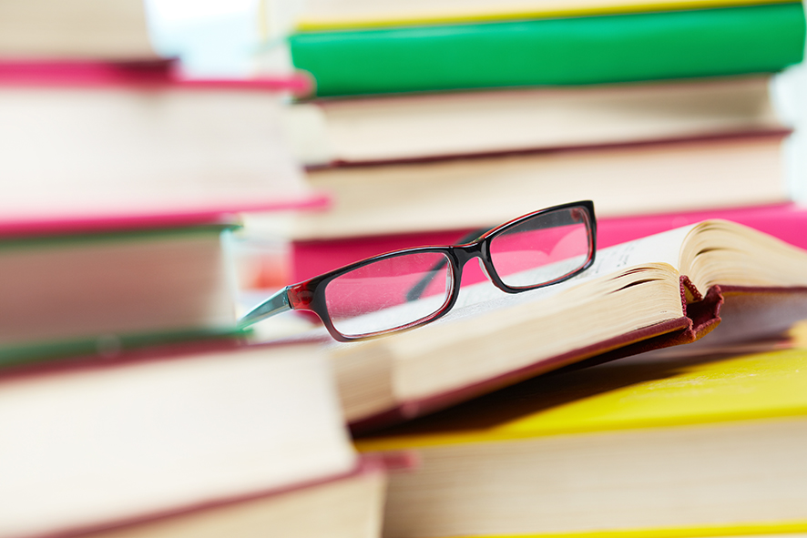 Close up image of glasses on pile of books: LASIK Sugery