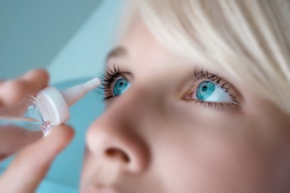 Lady applies eye drops for menopause and eye problems