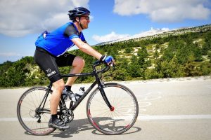 Man riding bike up a hill: sports and eye surgery
