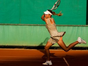 Tennis player hitting ball: sports and eye surgery